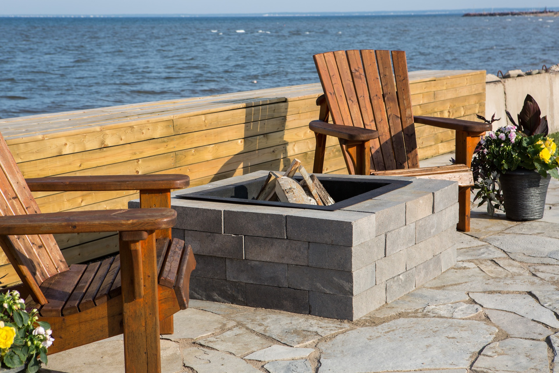 Ocean side backyard setting featuring Shaw Brick's Classic Weathered WallStone proucts around firepit