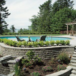 Backyard pool area featuring Shaw Brick's Roman Pisa retaining wall blocks