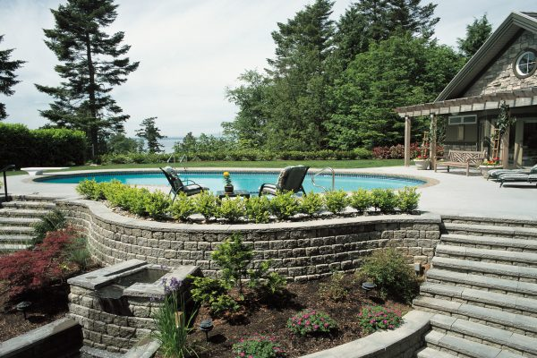 Backyard pool area featuring Shaw Brick's Roman Pisa retaining wall blocks