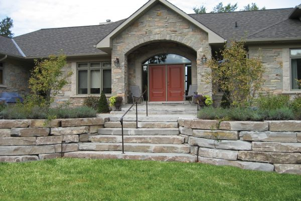 Front view of a house using Shaw Brick's Armour Stone in Mocha Limestone
