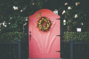 pink door with green and yellow wreath
